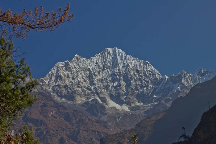 Everest Base Camp Day 2 - Kong De appears, framed by pines.