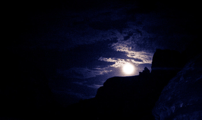 The moon rises behind a mesa in the Sinai Desert, Egypt.
