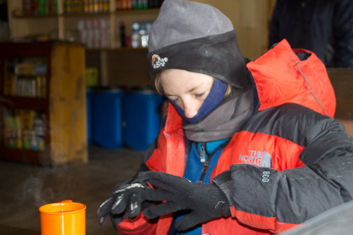 Everest Base Camp trek: in the warmest room at our lodge in Gorak Shep, Zac weighs the benefits of removing his gloves to warm his hands on his sea buckthorn juice.