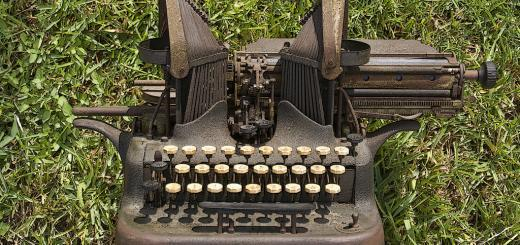 Old-fashioned typewriter on grass.
