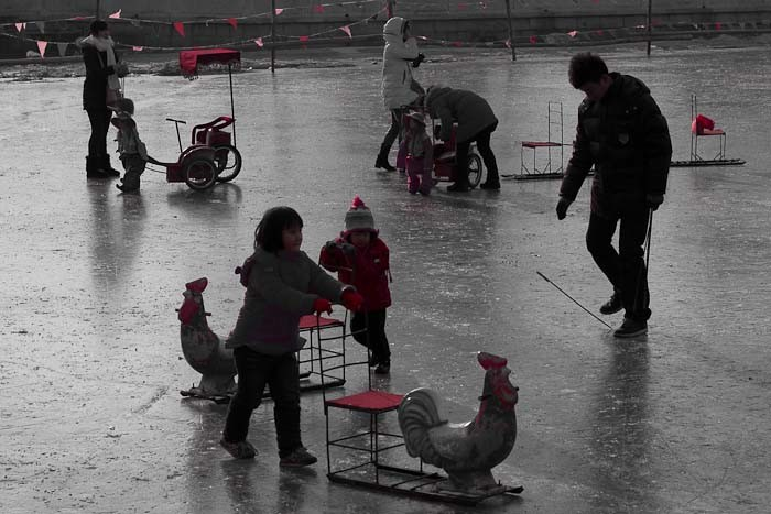 Ice skating in Beijing: little kids enjoying their skating chairs.