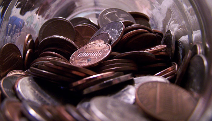 How to earn enough money to travel the world: jar full of pennies.