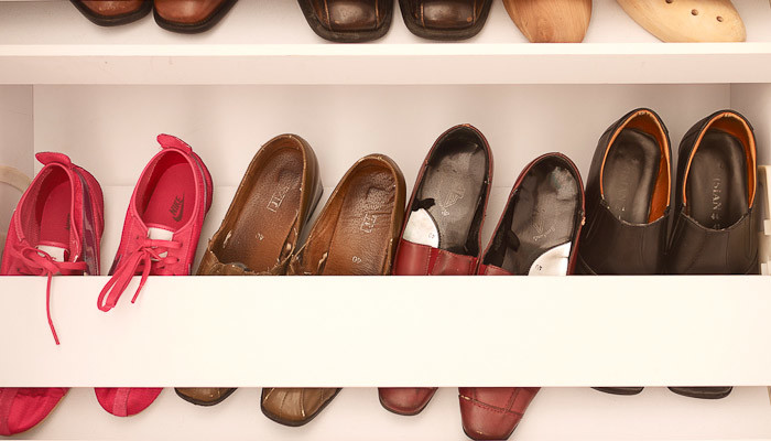 Lines of shoes in a shoe cupboard.