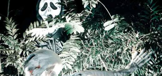 Child in scream mask over skeleton in bushes.