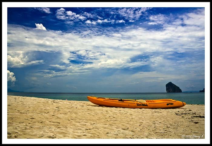 Sea kayak pulled up on an island off Krabi, by K Dimuraj.