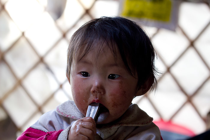 Mongolian toddler eating chocolate spread.