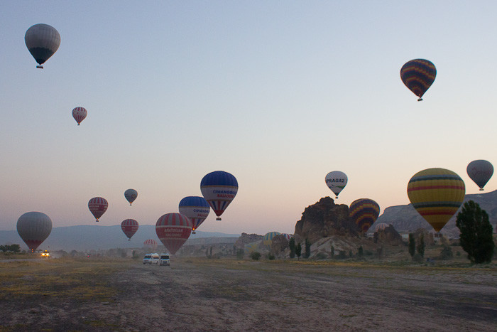 Hot air balloons rise with the sun above the lunar landscape of Cappadocia, Turkey.