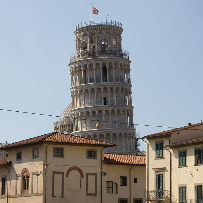 Leaning Tower of Pisa seen from the back, over buildings