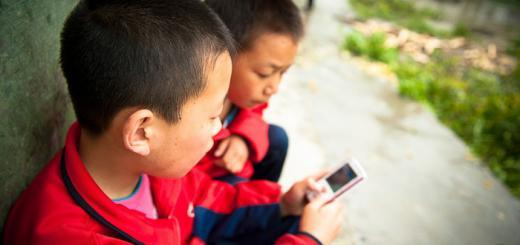 Primary school children in Liu Lin, Hubei, China, playing with a mobile phone.