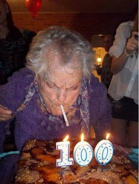 Elderly lady lighting cigarette from candles on birthday cake.