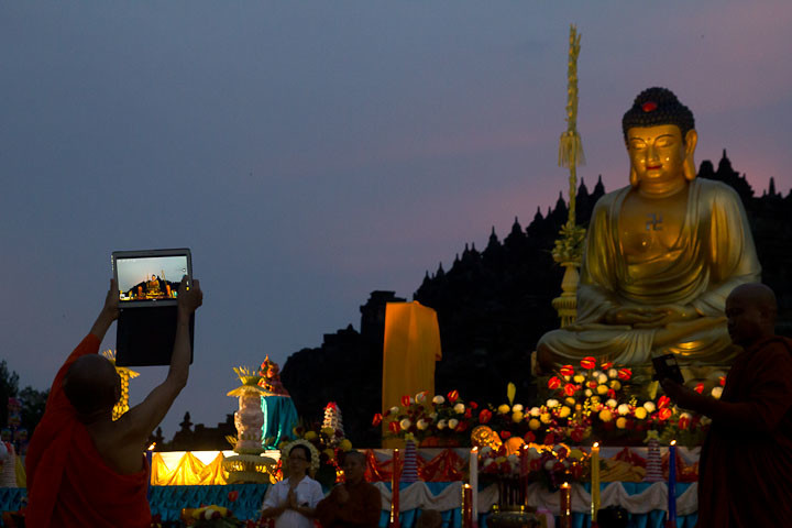 Buddhist monk takes a tablet photo of the altar at Borobudur during Waisak.