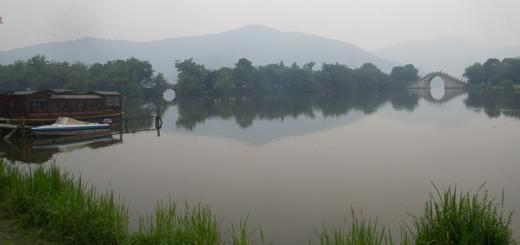 Boat, hills and bridge reflected in Xianghu Lake, Hangzhou.
