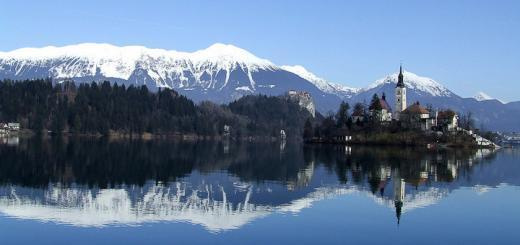 Lake Bled, Slovenia, with snow-capped mountains reflected in its waters.
