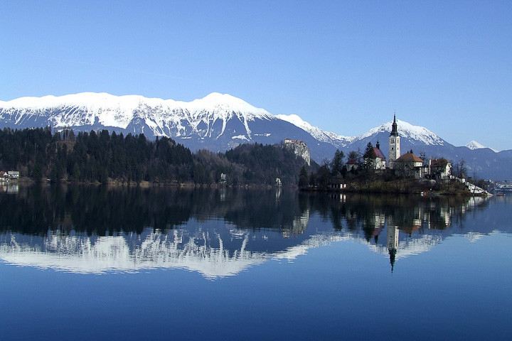 Lake Bled, Slovenia, with snow capped mountains reflected in the waters.