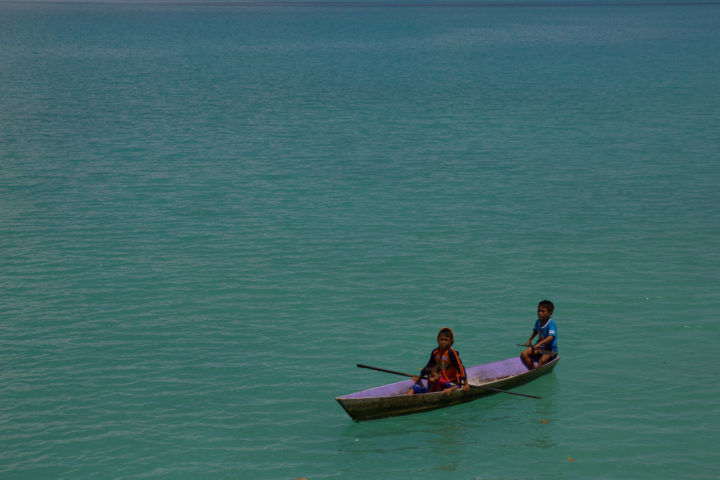 Children paddle a canoe in the Derawans, Borneo.