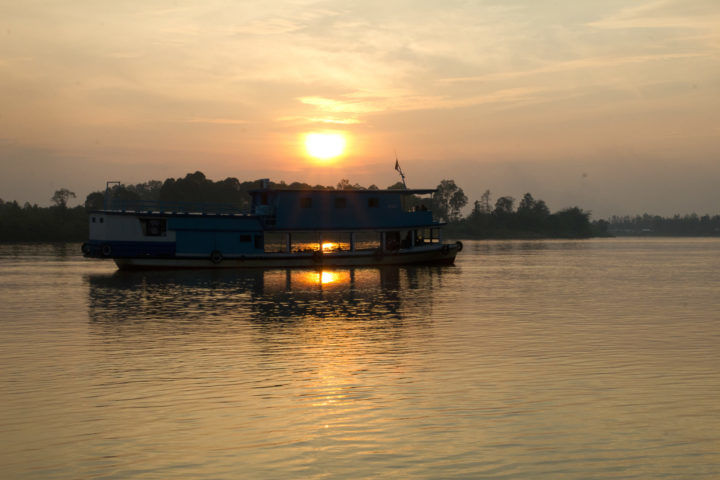 River boat against the setting sun on the Mahakam River, Borneo.