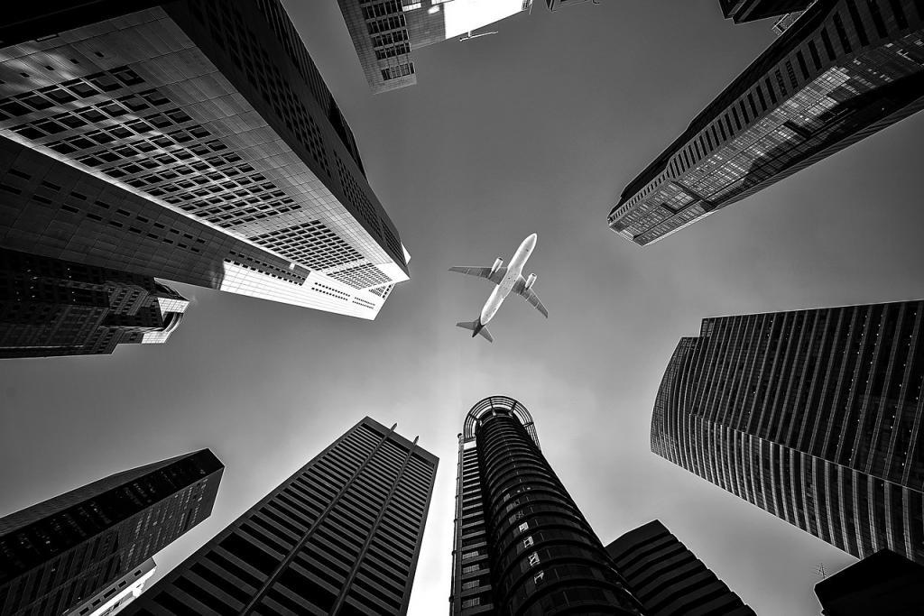 Aircraft between skyscrapers in black and white.